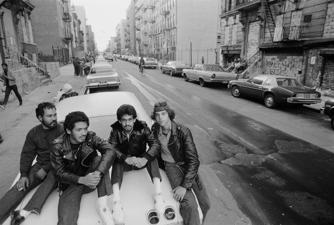 Tito (3rd from left) with friends in a street in Los Sures, Williamsburg, Brooklyn, New York, USA. Tito is one of the principal subjects of the 1983 documentary, Los Sures, about the predominantly Puerto Rican neighborhood and produced and directed by Diego Echeverria. Photograph made October 14, 1983.  (c) Ellen Tolmie 1983.  Written permission required to reproduce in any medium; permission also dependent on complete credit being given.